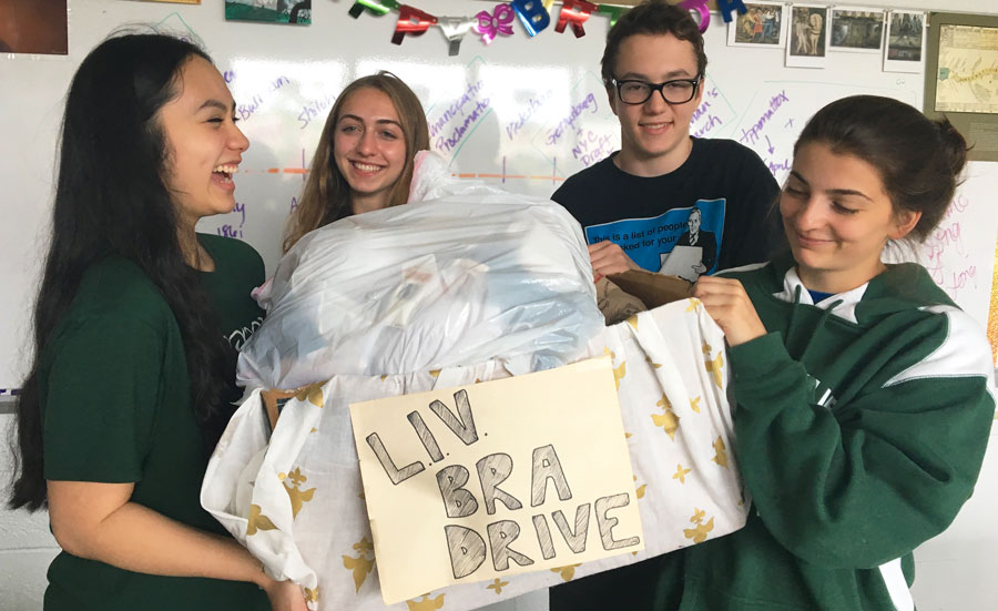 Bianca Belmonte, Julia Guskind, Aidan McBride, and Sam Nicklas hold up their bra donations.