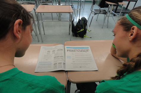 From left to right, sophmore Amy Santo and Carly Boyle take a peek at a PSAT booklet. SAT season can be a stressful time for students.