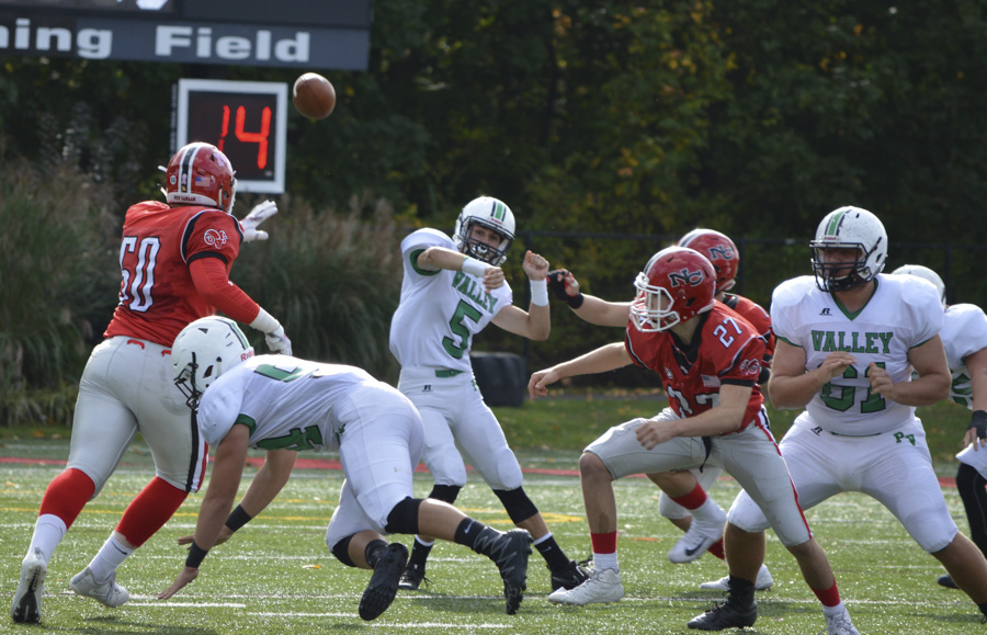 Junior quarterback Jake DeMilia (5) a gets off a throw as he is pressured by New Canaan defenders.