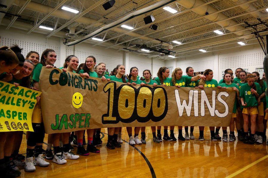 Players hold up a sign congratulating Jeff Jasper on his 1,000th win. Jasper joins a list of 41 other high school basketball coaches who have reached the 1,000 win milestone.