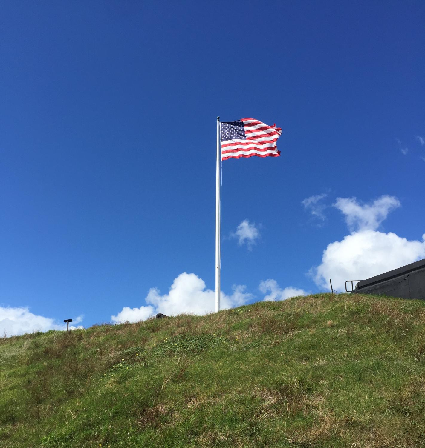 American flag stands up on a hill.