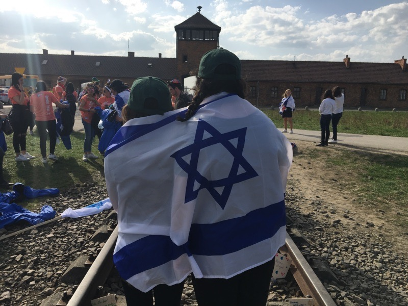 Ally+Botwinick+and+Julia+Ganbarg+with+the+Israel+flag+at+Birkenau.+They+recently+went+on+a+trip+to+participate+in+March+of+the+Living.+