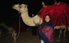 Angie DeLima standing with a camel in Dubai.