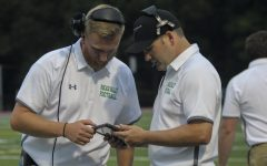 Assistant Coaches JJ Moran (left) and Adam Preciado review game footage on an iPad from the sidelines. On Friday, iPads and HUDL Sideline technology will be used to provide instant replay reviews during the game.