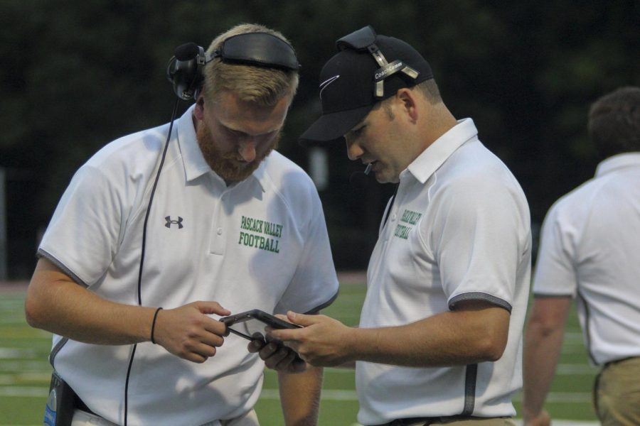 Assistant+Coaches+JJ+Moran+%28left%29+and+Adam+Preciado+review+game+footage+on+an+iPad+from+the+sidelines.+On+Friday%2C+iPads+and+HUDL+Sideline+technology+will+be+used+to+provide+instant+replay+reviews+during+the+game.