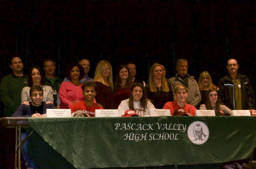 Matt Beyer, Justin Martin, Haleigh Marzano, Zach Olson, and Brianna Smith pose, along with parents and coaches. These five student-athletes took part in the National Signing Day ceremony on Wednesday in the Pascack Valley auditorium.