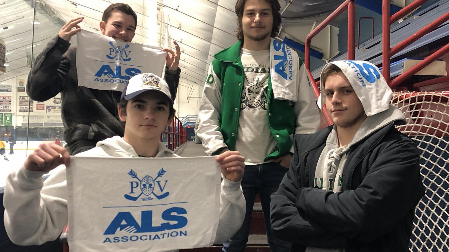 Senior hockey players Matt Mugno, Alex Sullivan, James, Gunther, and Zach Schneider pose with rally towels. The towels will be distributed to fans who bring a canned food item to Saturday's game.