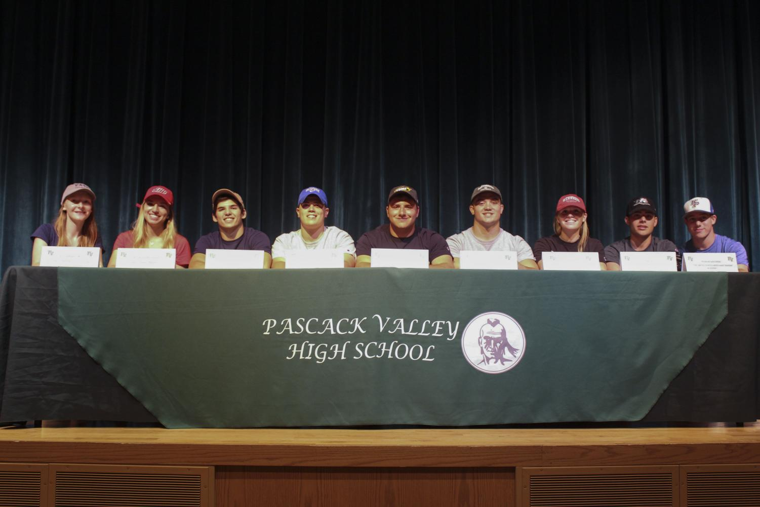 Nine seniors sit at the podium after deciding which college to commit to. Arianna Quevedo was unable to attend the event.