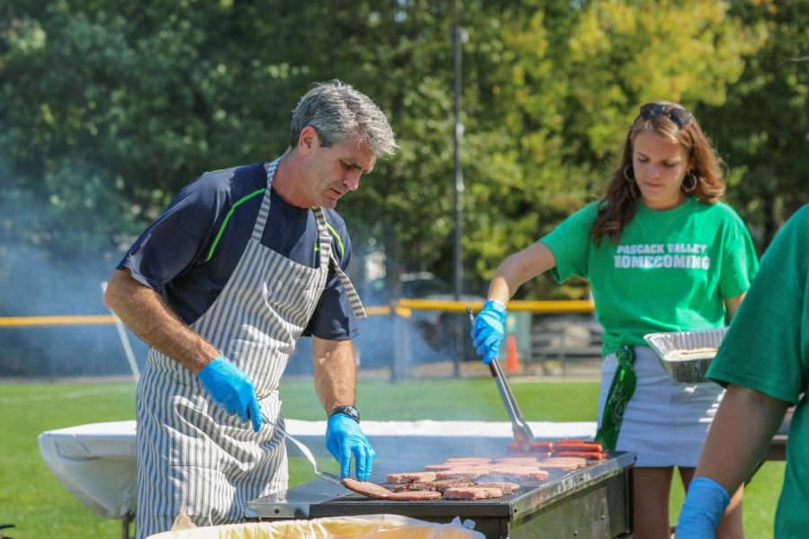 PV physics teacher Bill Koenig and senior and president of the homecoming committee Olivia Jones grill hamburgers and hotdogs during homecoming. The event was held adjacent to the football field from 11:30 a.m. to 3:30 p.m. on Saturday, Sept. 28.