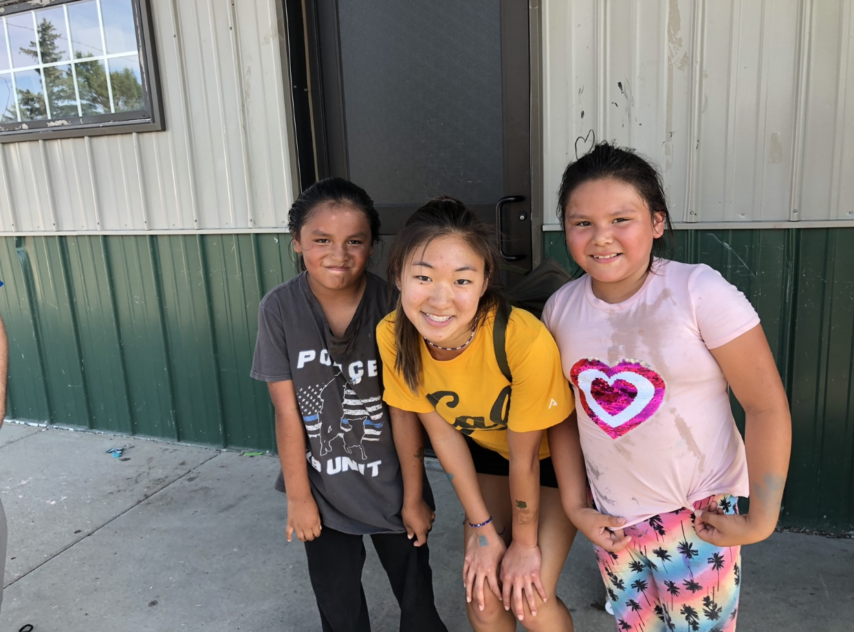 Junior Ellie Kim stands with two children outside of the Cheyenne River Youth Project building. She addresses the importance to give back to communities in need following the service trip to South Dakota.
