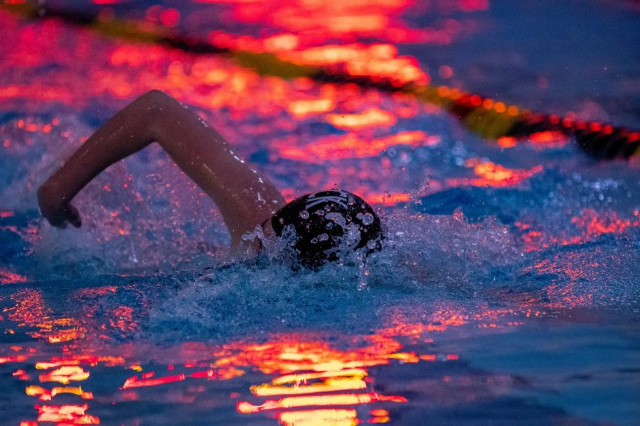 A+swim+team+member+cuts+through+the+water+under+the+lights+of+the+scoreboard.+Pascack+Swimming+defeated+Hackensack+on+Tuesday%2C+Jan.+7.