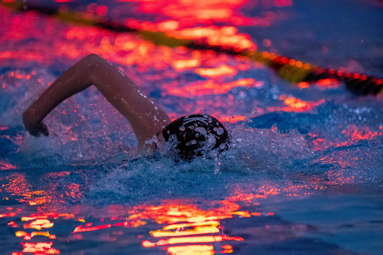 A swim team member cuts through the water under the lights of the scoreboard. Pascack Swimming defeated Hackensack on Tuesday, Jan. 7.