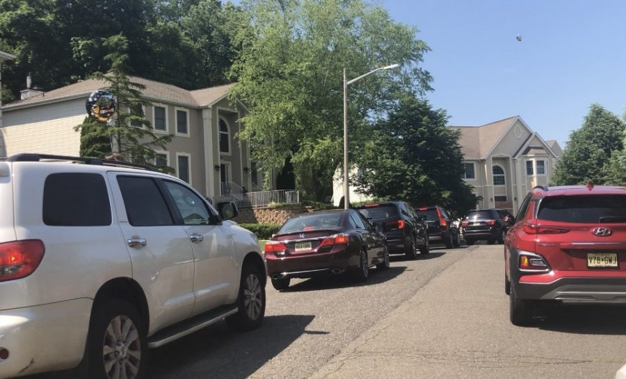 Cars wait before driving by homes.