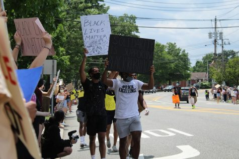 Protesters walk along Old Tappan Road. Many held signs advocating for the Black Lives Matter movement.
