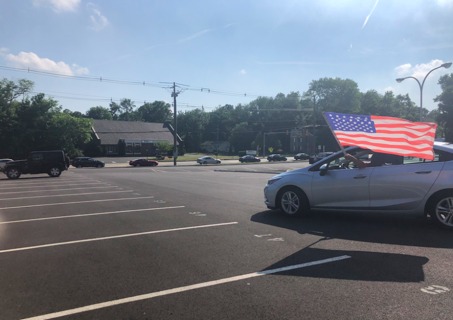 A car enters the parking lot waving the American flag.