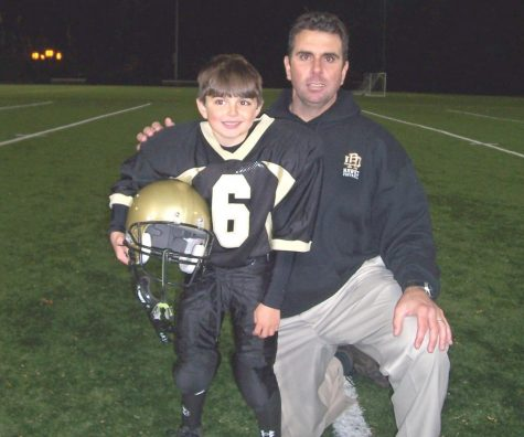 Glenn deMarrais posing with his son, who played junior football for River Dell. DeMarrais coached high school sports for almost 20 years before coaching his sons in Junior Football and Little League Baseball.