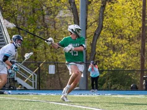 Jared Cohen attempts to keep the ball away from his opponent. The boys lacrosse team will look to reach the goals set by coach Matthew Will.