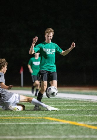 Ethan Schwartz chips the ball over the defender avoiding a slide tackle.